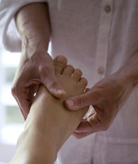 foot in hand of practitioner - a reflexologist